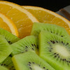 orange and kiwi on plate with knife
