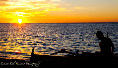 Sunset in Ilocos Sur, Philippines. The fisherman was just collecting his stuff in the boat.