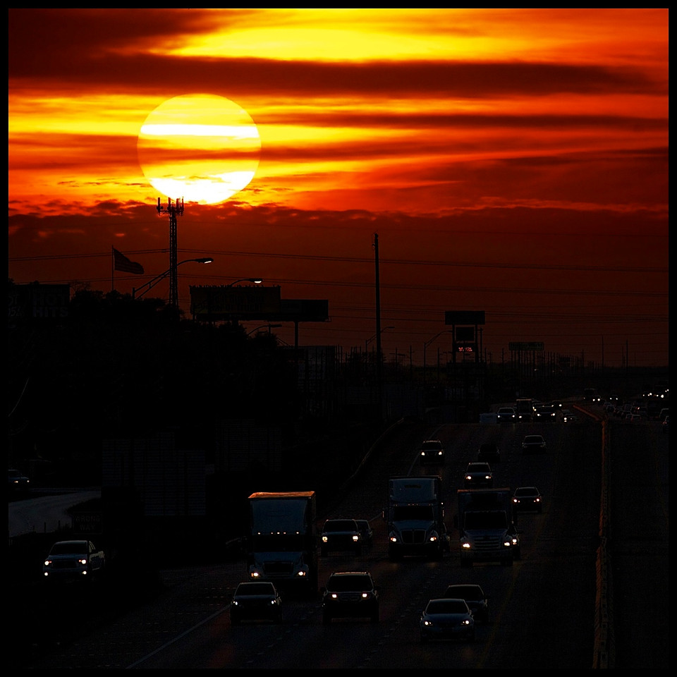 The sun sets behind commuters on I-10 in West Houston.