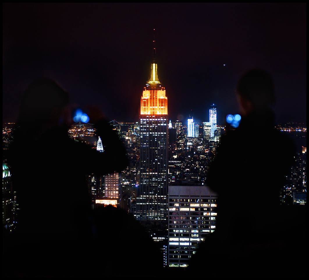 Two women taking picures of the Empire State Building from the Top of The Rock.