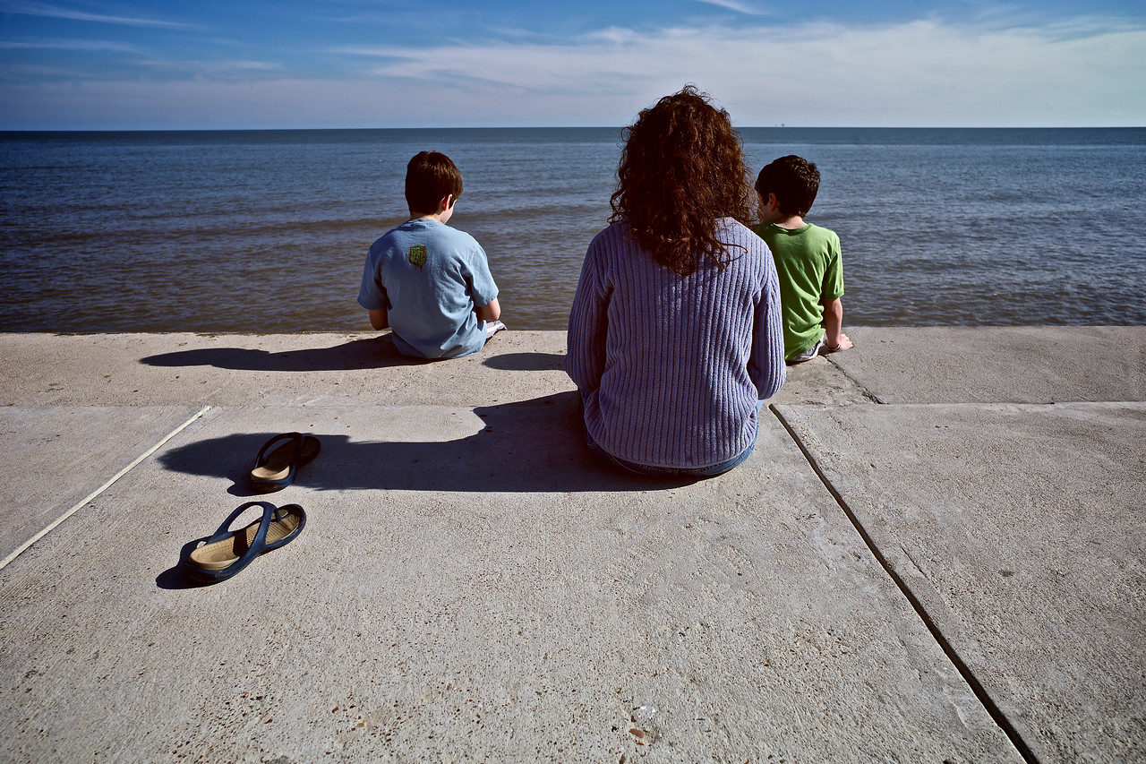 Darcy, Micah, and Ethan on the seawall overlooking the water.