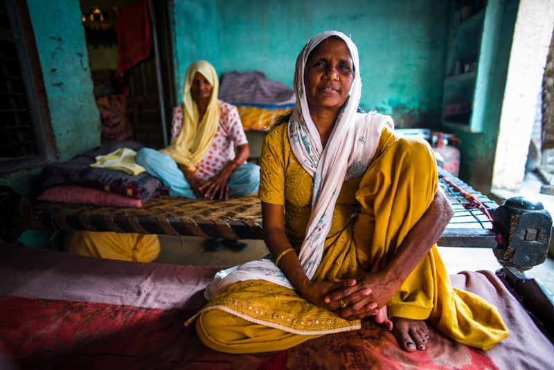 Two women rest on cots at a home in Punjab, India.