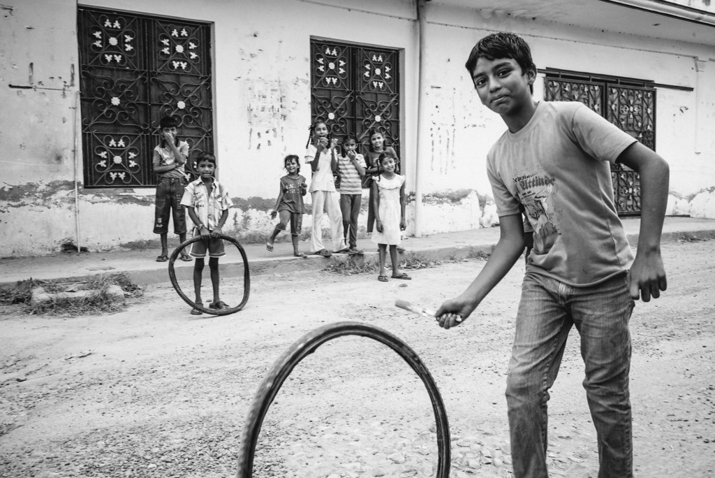 Children playing with tire inner tubes along a dirt street in Punjab, India.