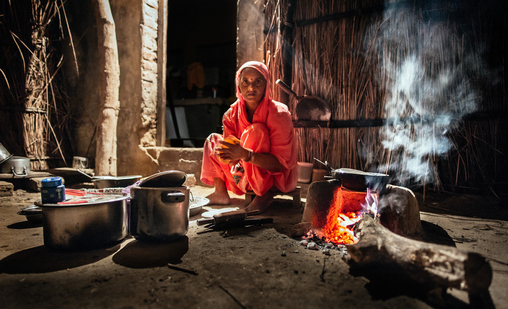A woman prepares an evening meal in a small hut. Punjab, India