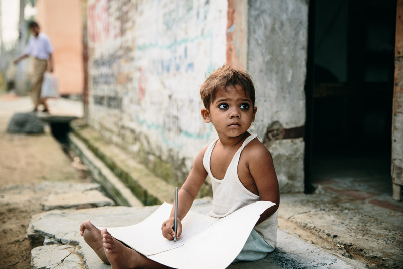 A young child sits and quietly draws in front of his home in Punjab, India.