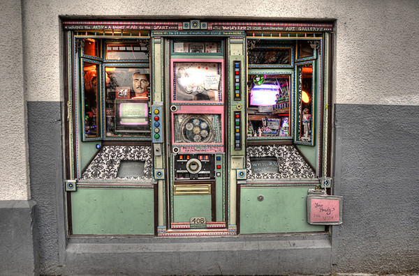 1228 oddity<br /> <br /> Finding oddities in Portland is easy ... normalcy would have been a more challenging theme.  Of all the many things to choose from, I'll post the Coin Operated 24-hour Church of Elvis.<br /> <br /> In it's heyday at a different location (next to Tugboat Brewery, Steven) the 'church' was a quite a draw. Coins dropped in a slot were rewarded with small bits of art, music or a digitized quote from Elvis himself.  For a slightly larger donation wedding certificates were available.<br /> <br /> Sadly today's 'church' has moved to the wall of a nondescript  building, and doesn't seem to have the same drawing power.  But hey, for a couple quarters you really can't go wrong ... and you might get a serenade from the King.