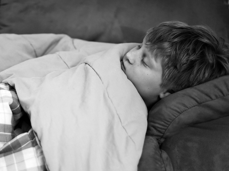 124 of 365 (John sleeping?)<br /> <br /> Not sure if he is fully awake or not but we were both watching something on the tv. Originally taken in colour but prefered this in b&w.<br /> <br /> 1/12 sec;   f/1.8;   ISO 400 hand held. This was also converted in camera to monochrome and to jpg so some detail has been lost.