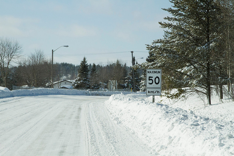 50 of 365 (Enough Already)<br /> <br /> On the drive home, seen this sign getting buried in the snow. If we get much more, I wont know how fast to drive.