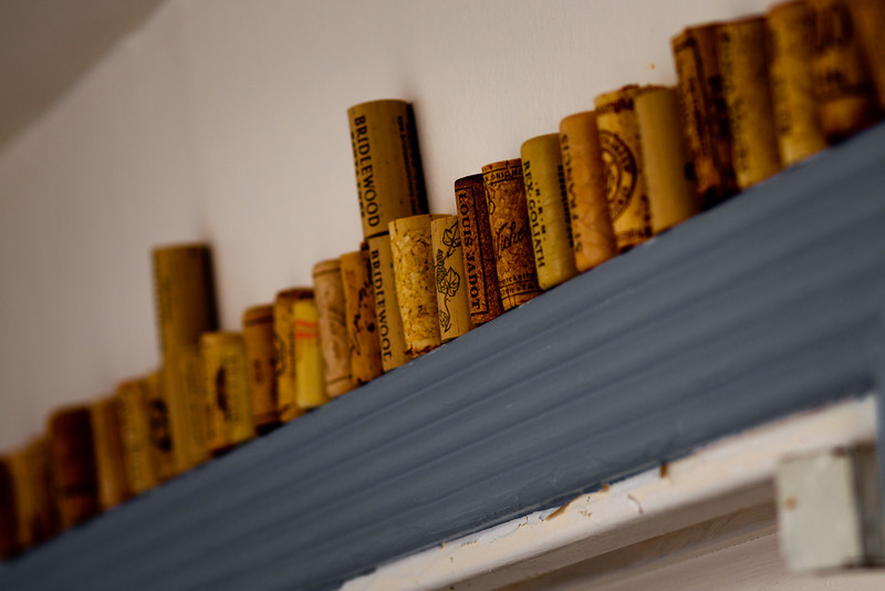 "Day 25. August 2, 2010. One of the most commented-on ""features"" of our house is our large collection of wine corks from our insatiable appetite for wine. Here is one of many high surfaces in the kitchen that has been taken over by the corks. This is also the first picture so far in this collection that used an off-camera flash. Hooray! The kitchen light was just terrible and cast very bland shadows, so I reflected a flash at 1/8 power off of the wall to the left.<br /> <br /> 85mm f/1.8 lens. f/4.5. 1/160. ISO 100."