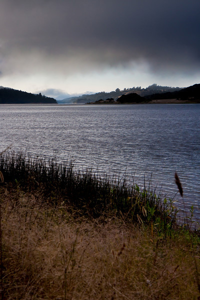 Day 28. August 6, 2010. On the way up to Half Moon Bay, we passed by Crystal Springs Reservoir, and the evening fog was a perfect balance between thin enough to let streaks of light through, and thick enough to make interesting patterns in the distance. Unfortunately, there wasn't a stopping are on the near side of the bridge, but we stopped on the far side and did some trespassing to get this angle. A little tricky to expose this correctly since the sky's still pretty bright low on the horizon. In post-processing, I removed the four power lines, added contrast to the sky, and brightened the foreground.<br /> <br /> (Update: Also, I just realized. This could totally be an ad for quite a few of the basic composition principles at work. Rule of Thirds, breaking the horizon, etc)<br /> <br /> (Update 2: Forgot to mention that I used a circular polarizer for this to have more control over the reflections off of the water.)<br /> <br /> 17-55mm f/2.8 IS lens @ 38mm. f/8.0. 1/125. ISO 200.