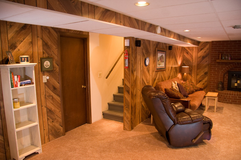 Basement family room with fireplace and carpet squares installed in 2011.  Stairs to main floor behind the sofa and wall.  Storage room behind the stairs and under the stairs.