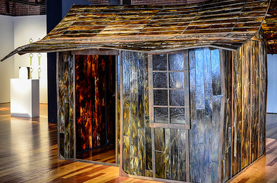 """1206 stained glass  Crystal Schenk's  """"Shelter"""" exhibit is a stained glass re-creation of an Appalachian shack, created to show the disparity between the 'haves' and the 'have-nots.'  Without knowing Ms. Schenk, I'll put her in the 'have' column."""