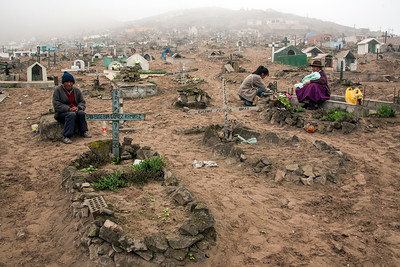 Nueva Esperanza Cemetery, located in the impoverished district of Villa Maria del Triunfo (Lima). Mourners pay respect while an elder offers prayers. Nueva Esperanza is the largest cemetery in Peru and the second largest in the world. Many graves are unmarked as low-income family members, unable to pay for a proper burial, must bury their loved ones late at night in clandestine graves.