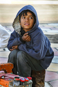 Young boy working as a shoe shiner on the streets of Bashra, Iraq