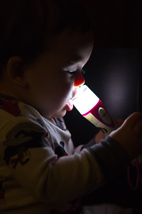12-28-2012. Noah trying to eat his sister's flashlight.
