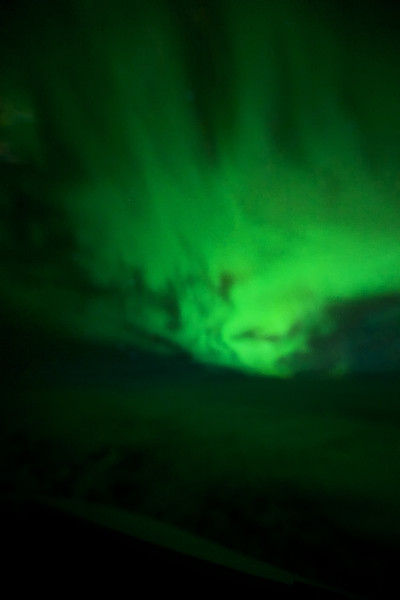 Northern Lights as seen from the cockpit of an Airbus A380. Somewhere between Iceland and Greenland on the way to New York. ISO 12800, f2.8, 1.6 seconds.Taken through a not very clean cockpit window, the nose of the aircraft is visible at the bottom of the picture.
