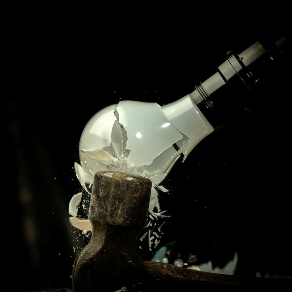 Frosted glass in incandescent makes contact with a hammer head and breaks