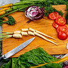 Sliced vegetables on a wood cutting board with a knife
