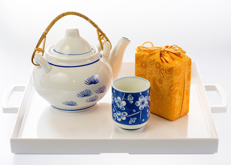 Teapot and cup with a package of tea