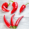 Sweet Red-Hot peppers six of them arranged on a tabletop