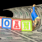 Man hanges from money with words LOAN