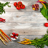 Collection of colorful vegetables form a frame on a weathered wood tabletop