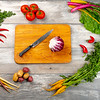 Many different vegetables forming a frame with a cutting board in the middle