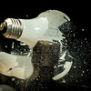 Hammer smashes an incandescent light bulb in the dark