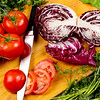 Assortment of vegies Cabbage and tomatoes sliced on a wood cutting board