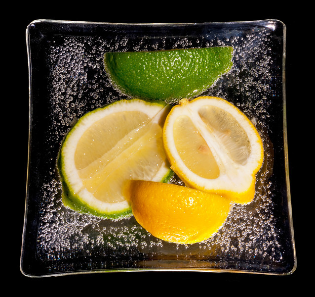 On a plate with tonic water bubbling are limes and lemons