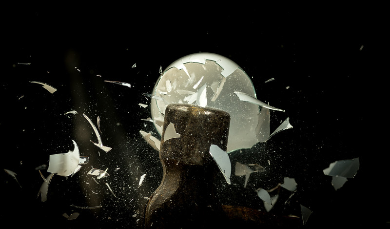 Shards of glass come off of a smashing light bulb as they hit a hammer