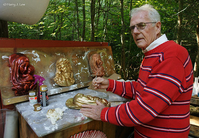 Ed at his workbench. He continues to produce the statues even though soon he will have no place to store them.