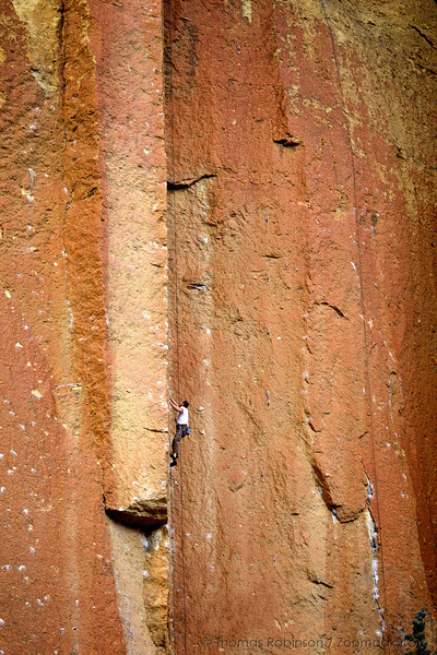 """A rock climber ascends the massive walls of Smith Rock State Park. These rocks are called """"welded tuff"""" formed from volcanic ash compressed with extreme heat and pressure. This solid of rock makes it one of the best rock climbing locations in Oregon."""