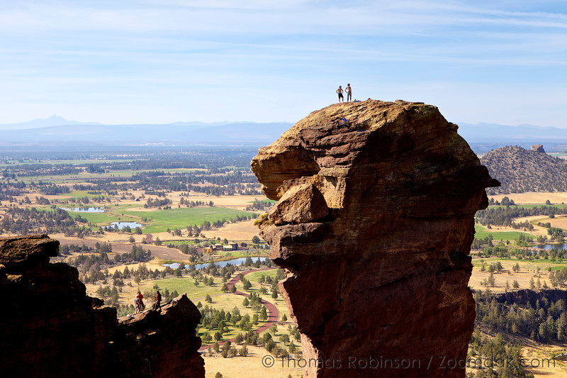 Two climbers stand as conquerers of Monkey Face in Smith Rock State Park, one of the best rock climbing locations in Oregon.