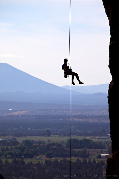A climber rappels down the line, seeming to recline on air, at Monkey Face in Smith Rock State Park with the Oregon Cascades in the background.