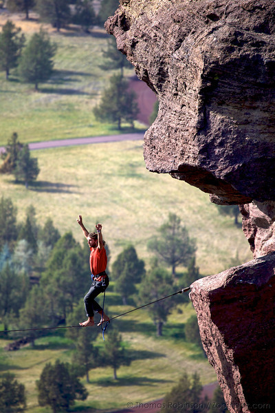 A professional slack-liner crosses the highline gap between Monkey Face and Misery Ridge in Smith Rock State Park- extreme slacklining.