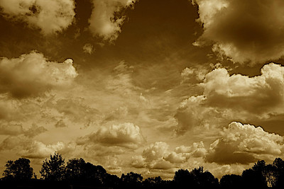Clouds in the sky over a park in Upper Arlington, Ohio on a September day in a sepia edit