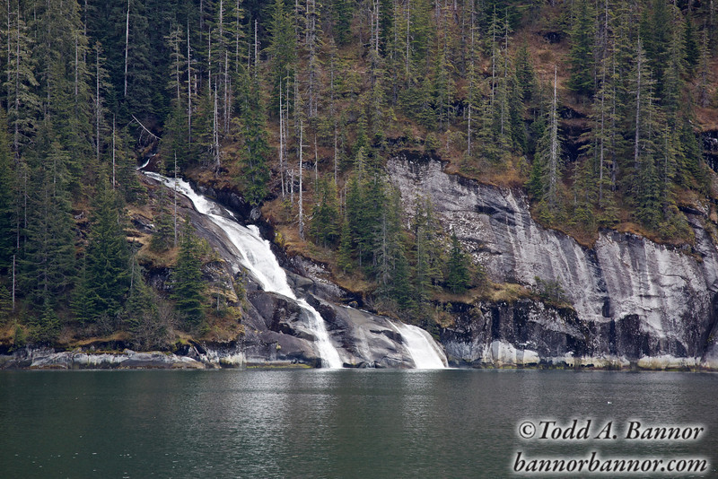 An unnamed waterfall spills into the fjord.