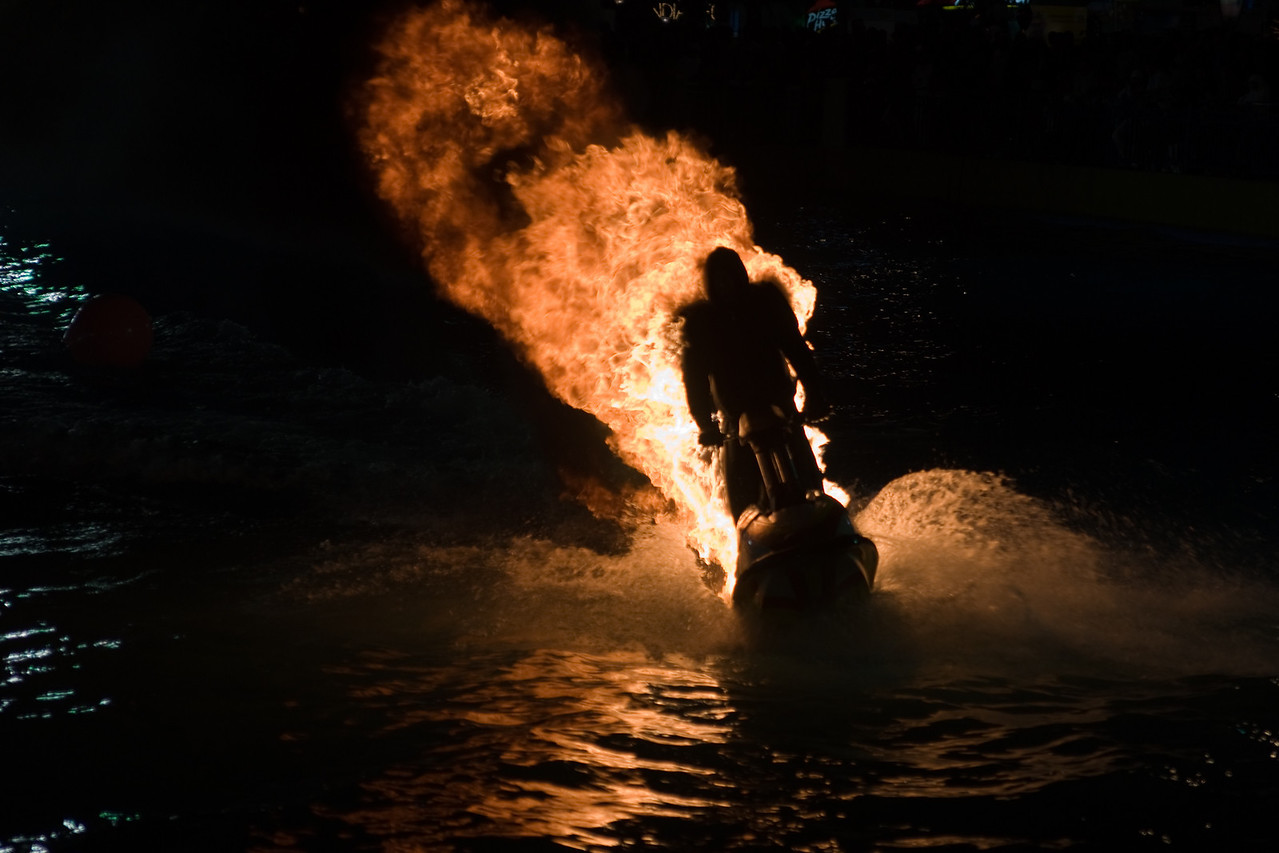 023. 12 December 2008 - Human Torch<br /> <br /> Well, you just don't see that everyday! I was stunned to see this! This guy, riding on a jetski, actually sets himself on fire and does a large lap around a lake, and then does a ramp/jump/dive underwater to extinguish the fire. And you could so feel the heat when he came past! <br /> <br /> I actually had another daily lined up, until I captured this, and felt that it needed sharing!<br /> <br /> Taken with my shiny new Carl Zeiss lens.