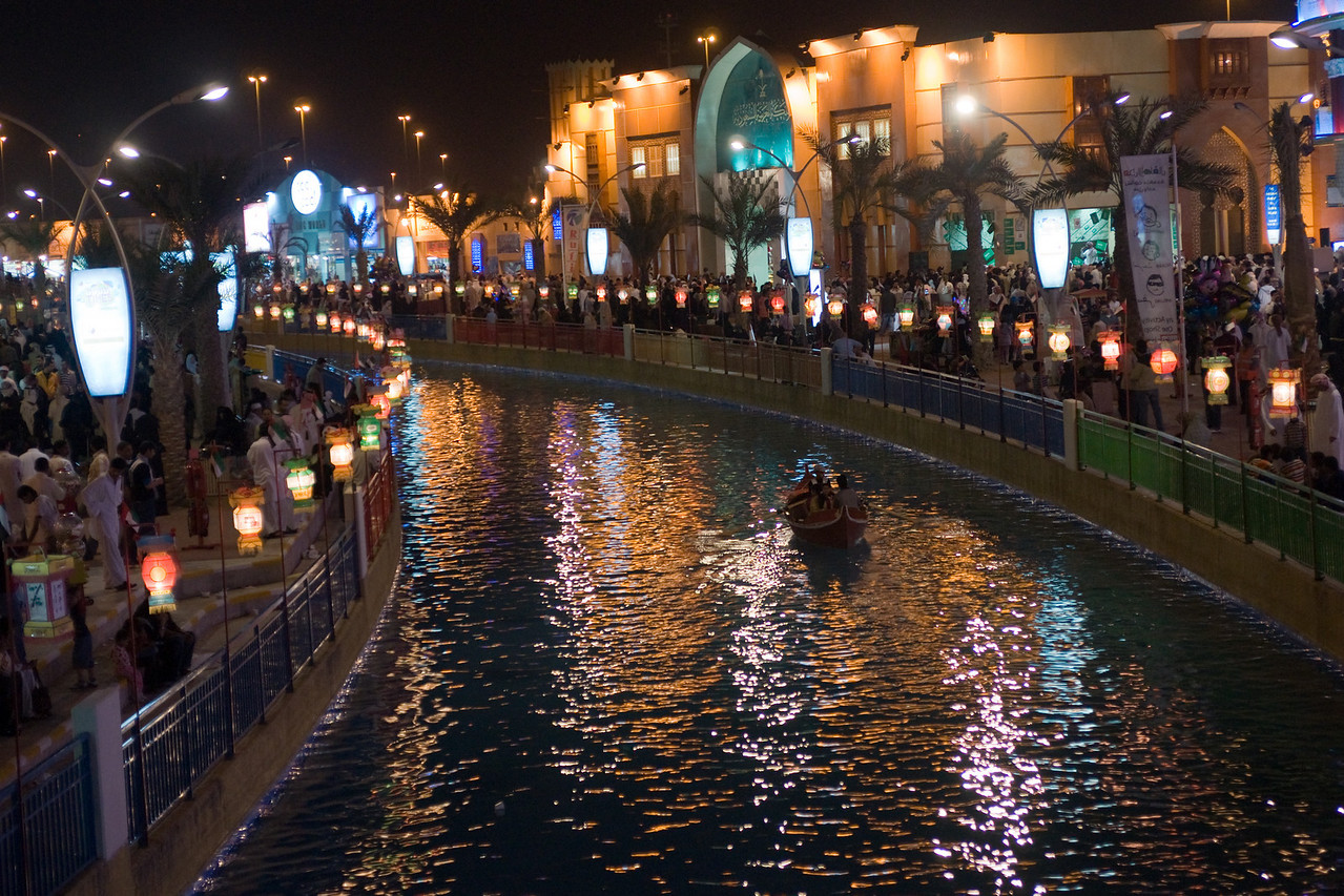 "027. 16 December 2008 - River of Light<br /> <br /> Back to Global Village, and this scene set on a bridge looking down river. Global Village is open for 3 months of the year (winter), and features pavilions from countries around the world. In these pavilions you can buy various goods generally produced in those countries... though I suspect most of it is still ""Made in China"". <br /> <br /> You will notice the Chinese lights featured in one of my previous dailies running all along this artificial river. What I really liked about this shot is how all the colors seem to blend reflecting off the water. <br /> <br /> Hope you enjoy it too."