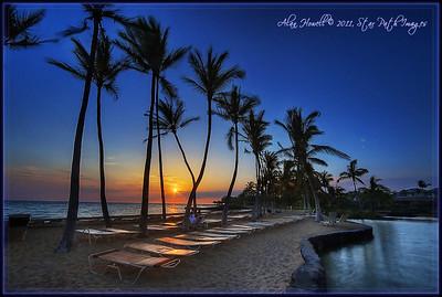 Sunset and palm trees in Kona, Hawaii.
