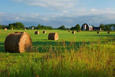 Haybales and farmhouse, Wisconsin