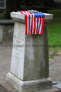 Paul Revere's Headstone in Granary Burying Ground on Tremont Street in Boston, MA with flag.