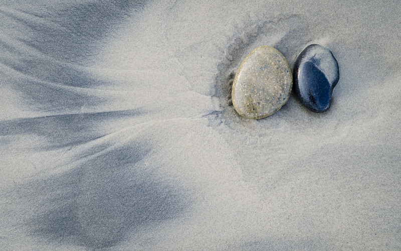 Two pebbles on a beach making amazing patterns in the sand.