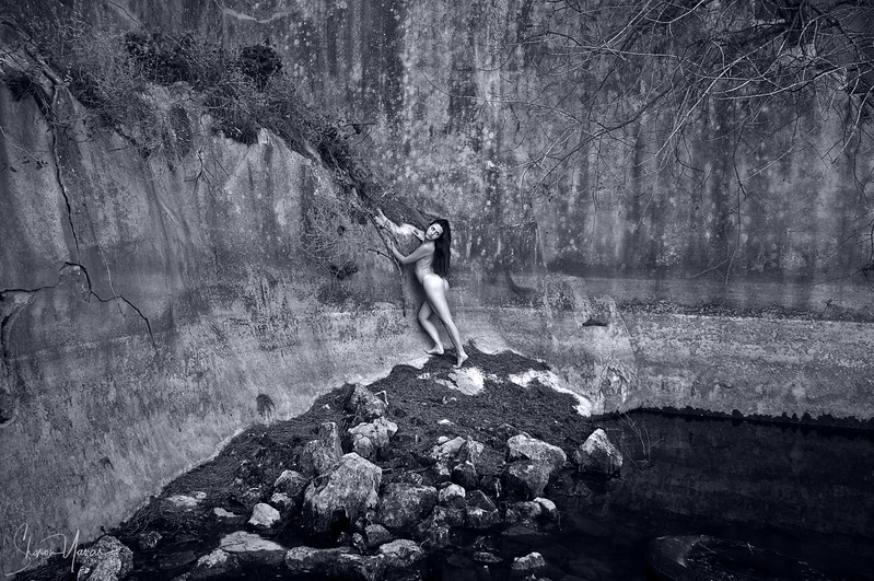 Naked woman alone outside standing on rocks