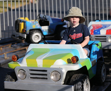 Brayton Walter of Grafton, 3, drives a mini-jeep at the Queen of Peace Festival in Grafton. RAY RIEDEL/CHRONICLE