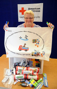 Linda Taylor,  a Red Cross volunteer from Lorain, and leader for the pillowcase project, holds a pillowcase above emergency preparedness items at the American Red Cross in Elyria on Aug. 12. STEVE MANHEIM/CHRONICLE