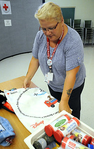 Linda Taylor,  a Red Cross volunteer from Lorain and leader for the pillowcase project, folds a pillowcase next to emergency preparedness items at the American Red Cross in Elyria on Aug. 12.  STEVE MANHEIM/CHRONICLE