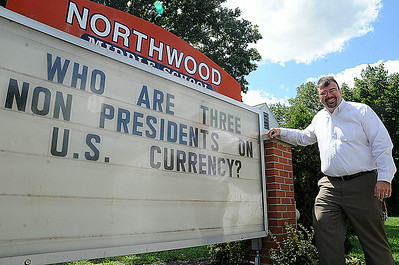Michael Basinski, principal at Northwood Middle School, stands next to the sign at the school's entrance on Gulf Road.  He poses questions for drivers to ponder while waiting at the traffic light. STEVE MANHEIM/CHRONICLE