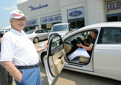 Nancy Mathewson, of Doylestown, formerly of Elyria, picks up the 2014 Ford Fusion she won with a ticket in the St. Jude Dream Home giveaway event at Nick Abraham Ford in Elyria on Aug. 7.  At right is her husband, Bob, a retired Elyria firefighter. STEVE MANHEIM/CHRONICLE